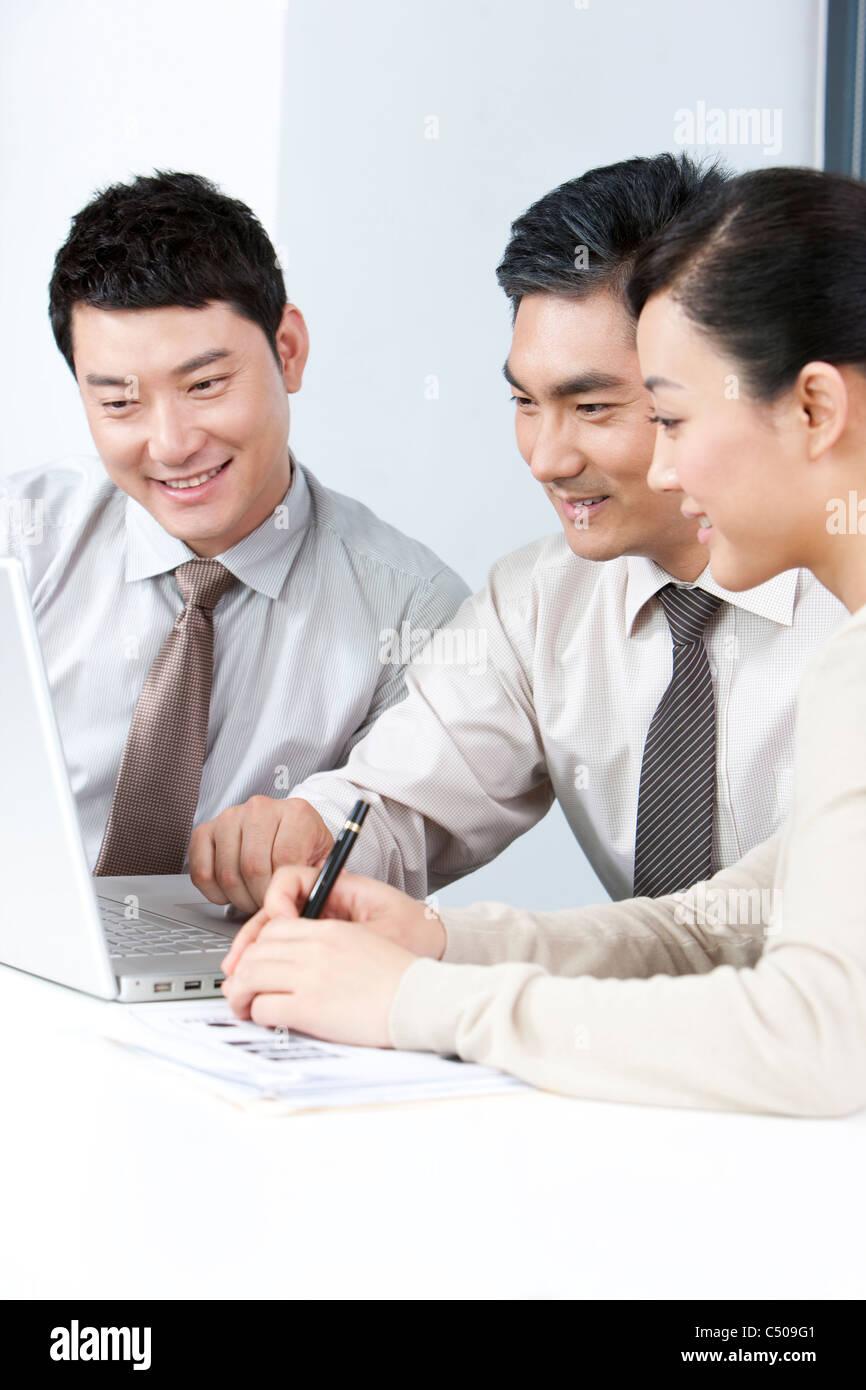 Ejecutivos de negocios, mostrando los jóvenes empresarios algo en el equipo Foto de stock