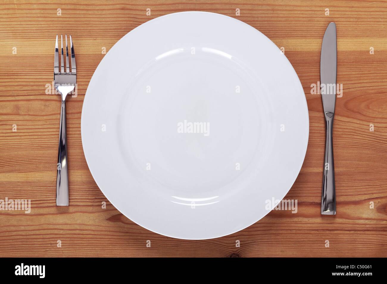 Foto de un plato blanco vacío con cuchillo y tenedor en una mesa de madera rústica. Imagen De Stock