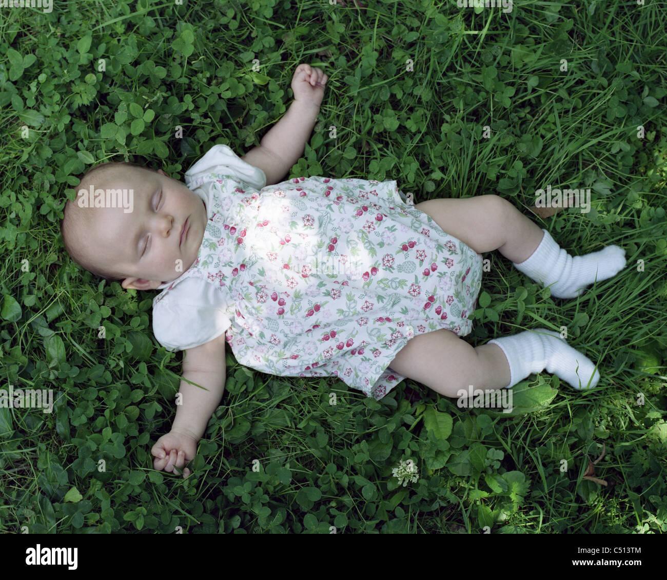 Bebe Durmiendo sobre el césped Imagen De Stock