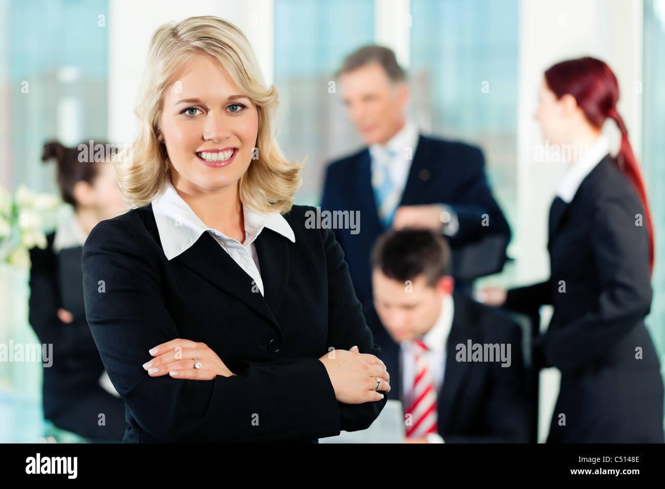 - Encuentro de negocios en una oficina; un colega está mirando a la cámara. Imagen De Stock