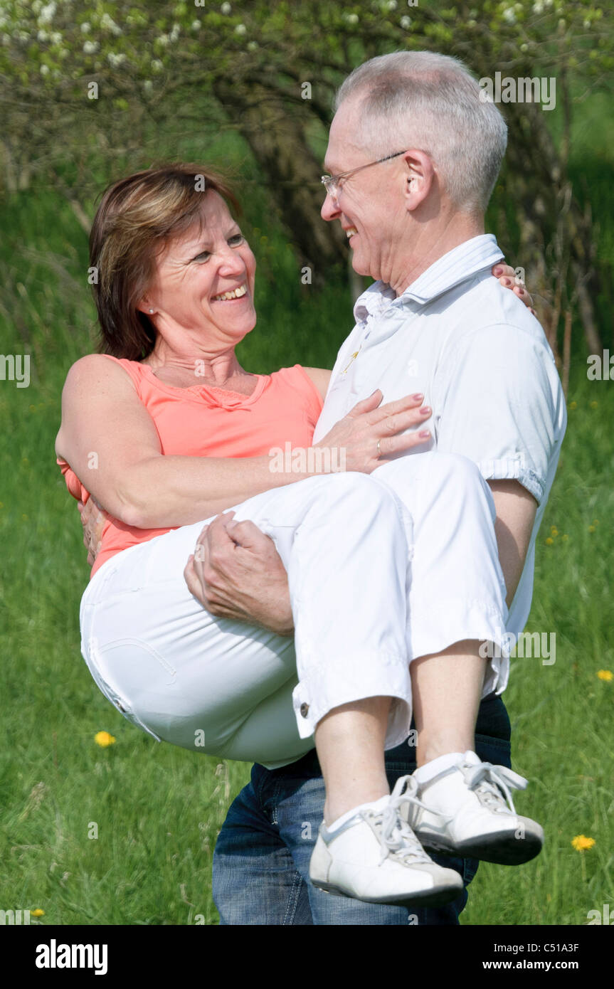 Pareja de mediana edad, el hombre lleva en sus brazos a una mujer Imagen De Stock
