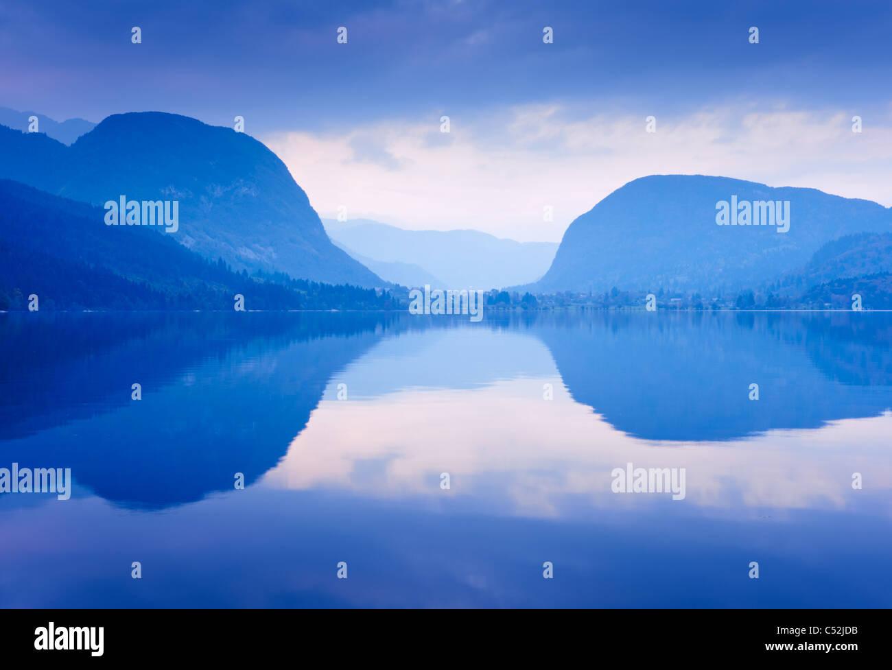 Montañas azules se reflejan en el agua del lago. El lago Bohinj, Eslovenia. Imagen De Stock