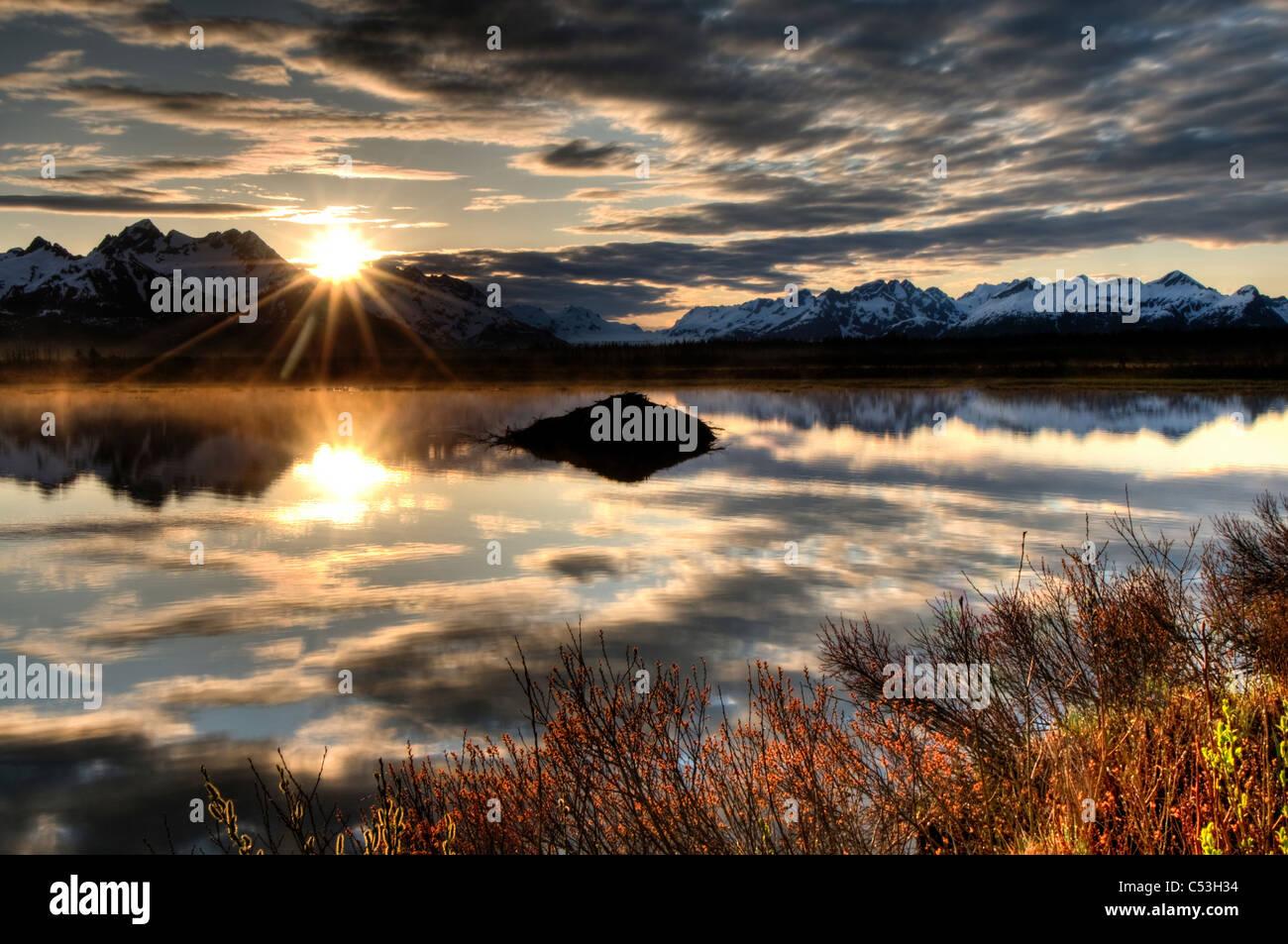 Sol se eleva sobre las montañas Chugach con un estanque y beaver lodge en primer plano, Bosque Nacional Chugach, Imagen De Stock