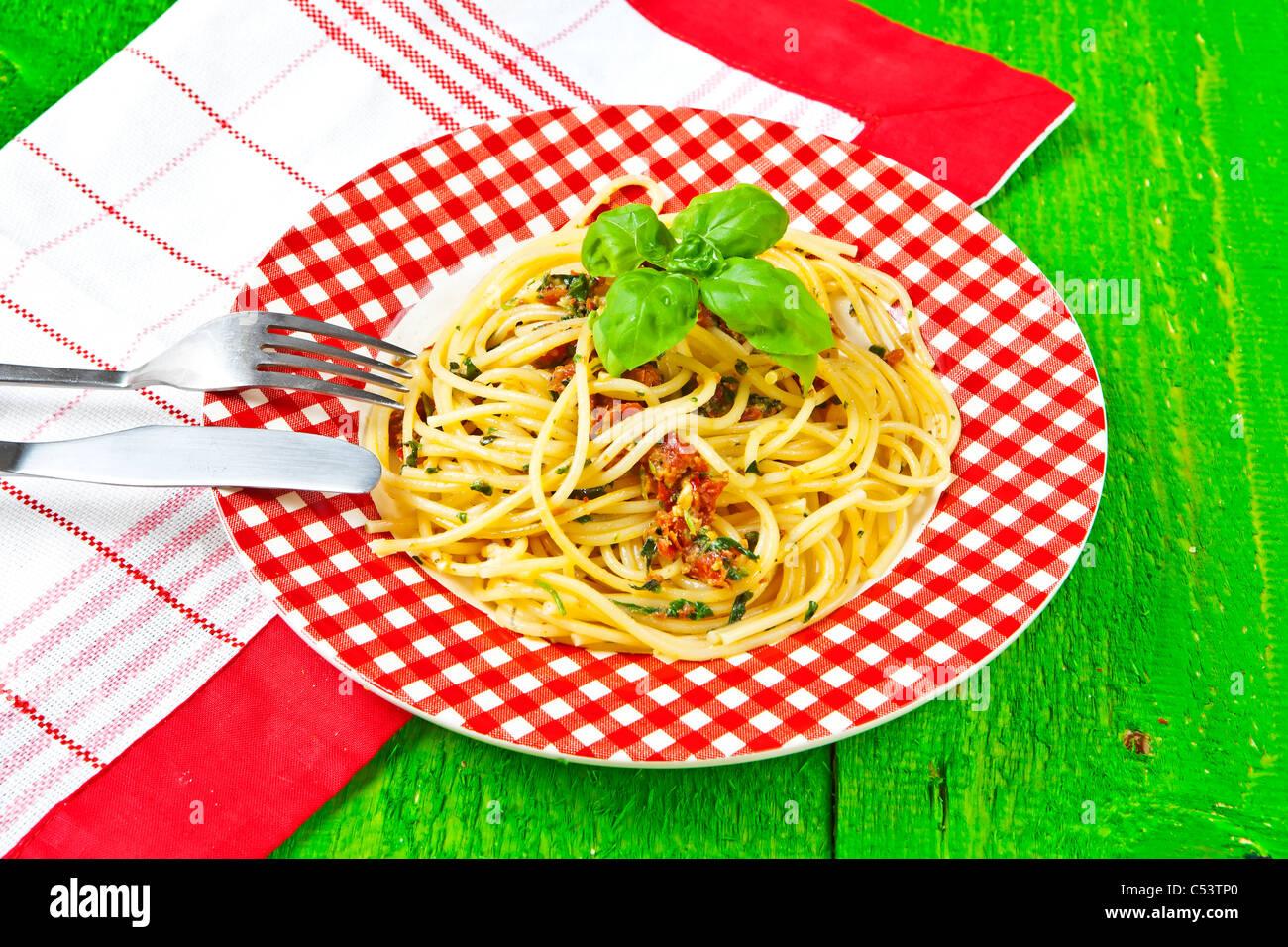 Espaguetis con pesto, hecha de tomates secos, queso grana, pecorino, rúcula, albahaca, piñones y ajo. Imagen De Stock