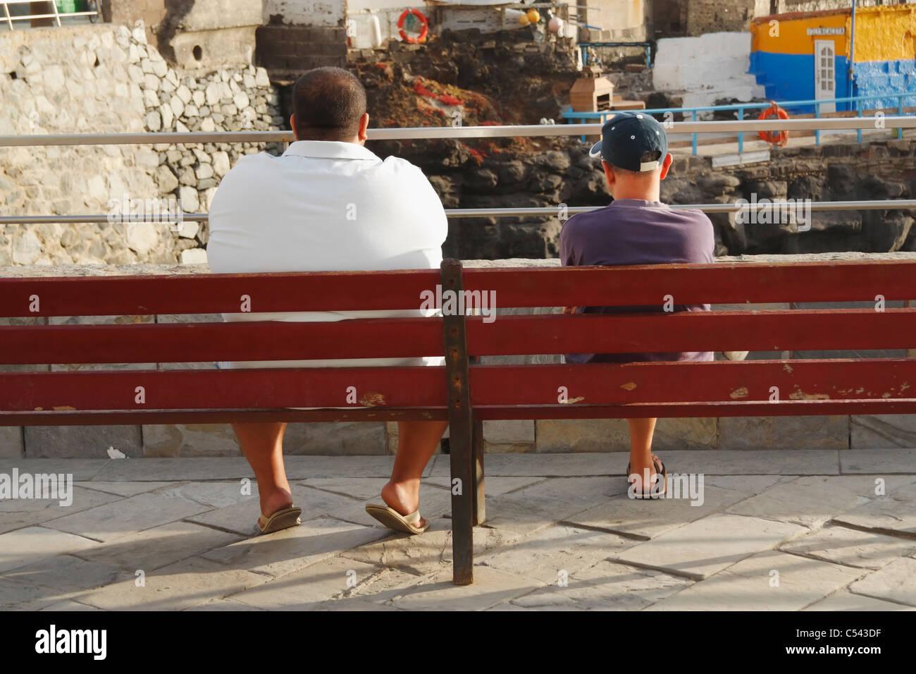 Gran hombre y pequeño hombre sentado en un banco en España Imagen De Stock