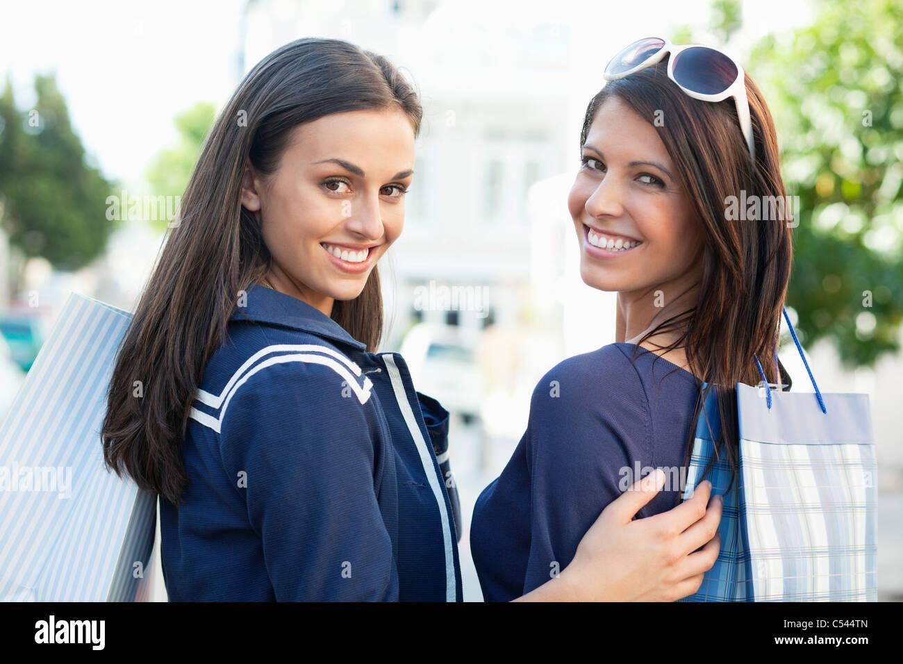 Retrato de dos jóvenes mujeres de pie con bolsas de la compra. Imagen De Stock