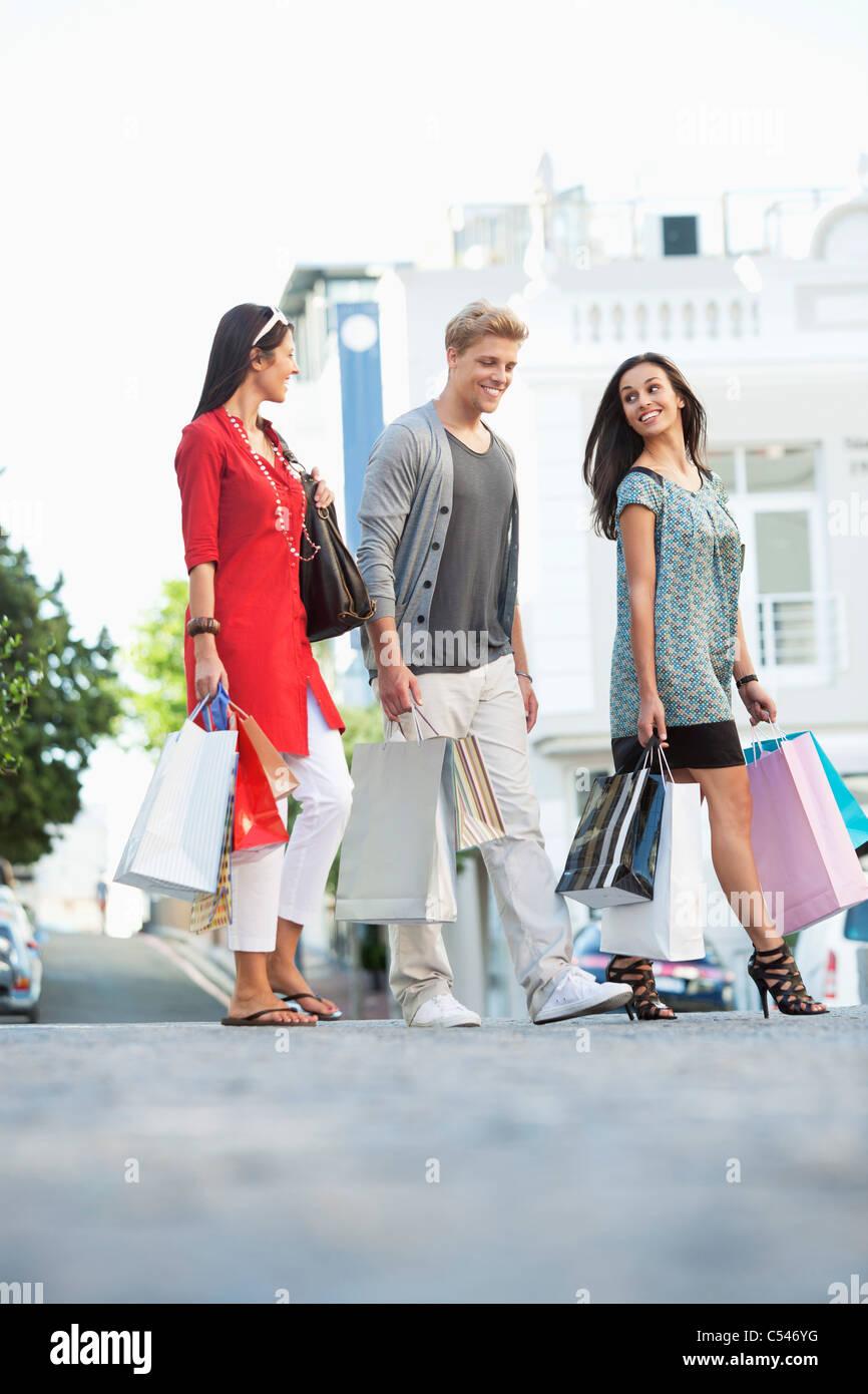 Joven con dos mujeres caminando con bolsas de la compra. Imagen De Stock