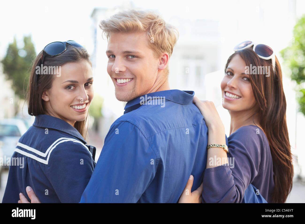 Retrato de un joven con dos mujeres sonriendo Imagen De Stock