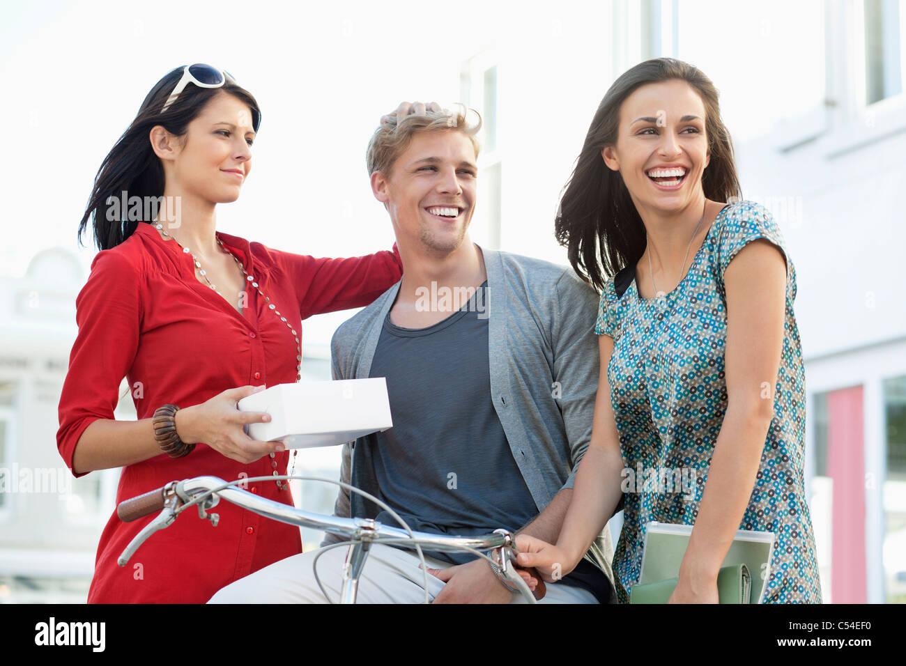 Sonriente joven con dos mujeres ciclismo Imagen De Stock