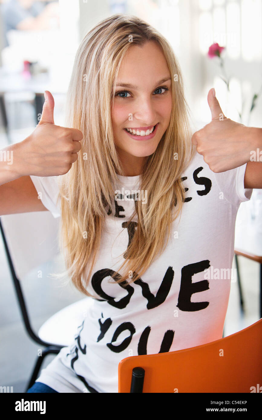 Retrato de una hermosa mujer mostrando Thumbs up en un café Imagen De Stock
