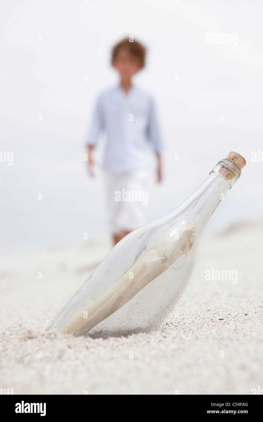 Muchacho caminando hacia borrosa botella con nota dentro en la playa Imagen De Stock