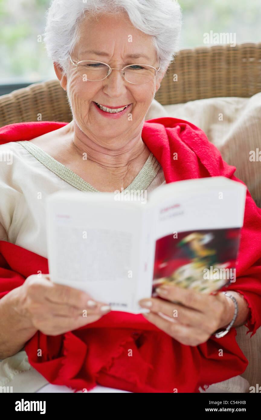 Senior mujer leyendo una revista y sonriente Imagen De Stock