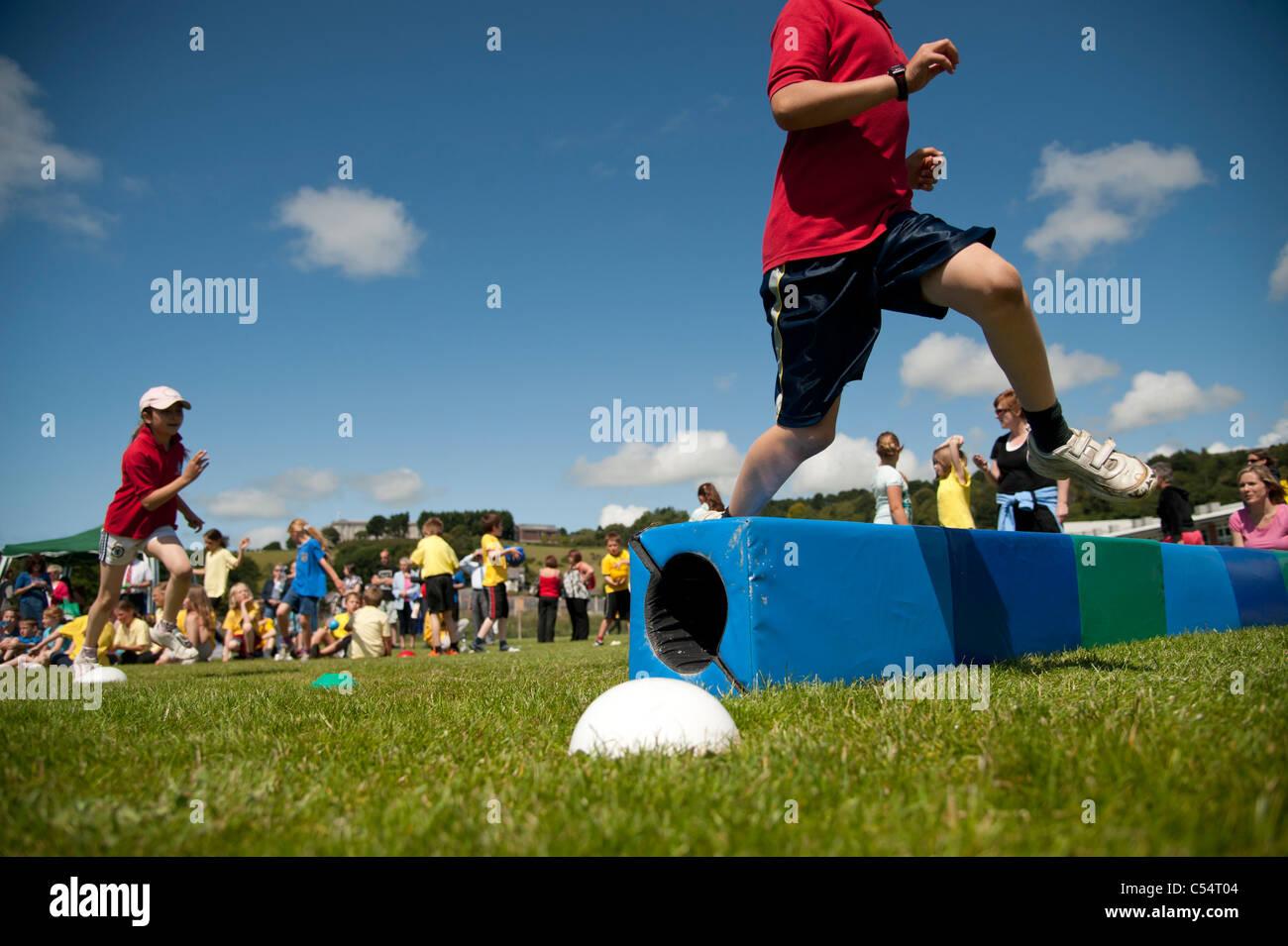 Los niños en la escuela anual día deportivo en una pequeña escuela primaria, UK Imagen De Stock