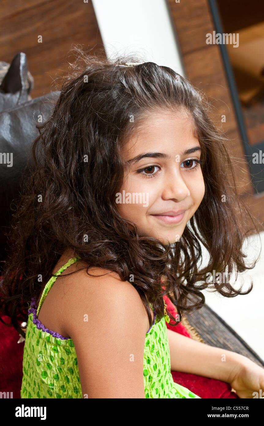 Hermosa chica étnicos sentado en un sofá mirando lejos Imagen De Stock