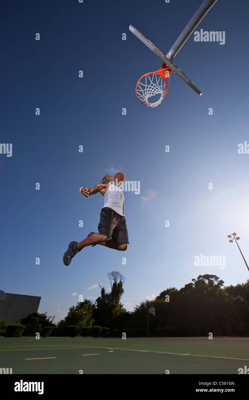 Macho haciendo slam dunk durante el juego de baloncesto al aire libre Foto de stock