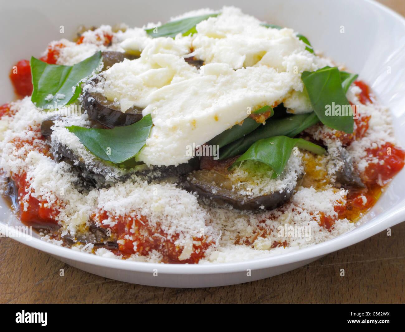 Melanzane alla parmesana porción individual en un plato blanco en una mesa de madera, cocina tabla de cortar listo Foto de stock