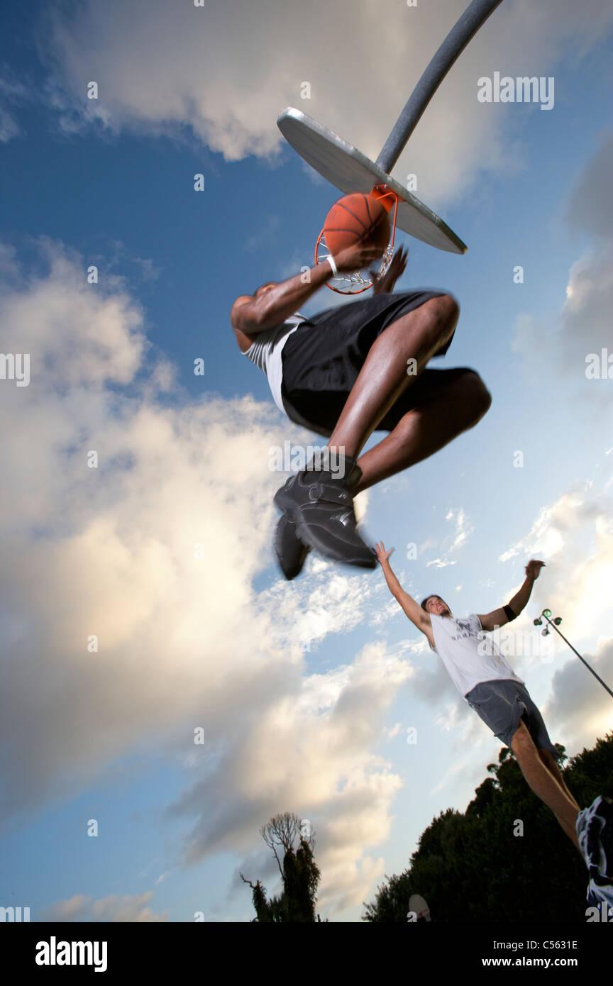 Puntuación masculina durante el juego de baloncesto al aire libre, vista desde debajo Foto de stock