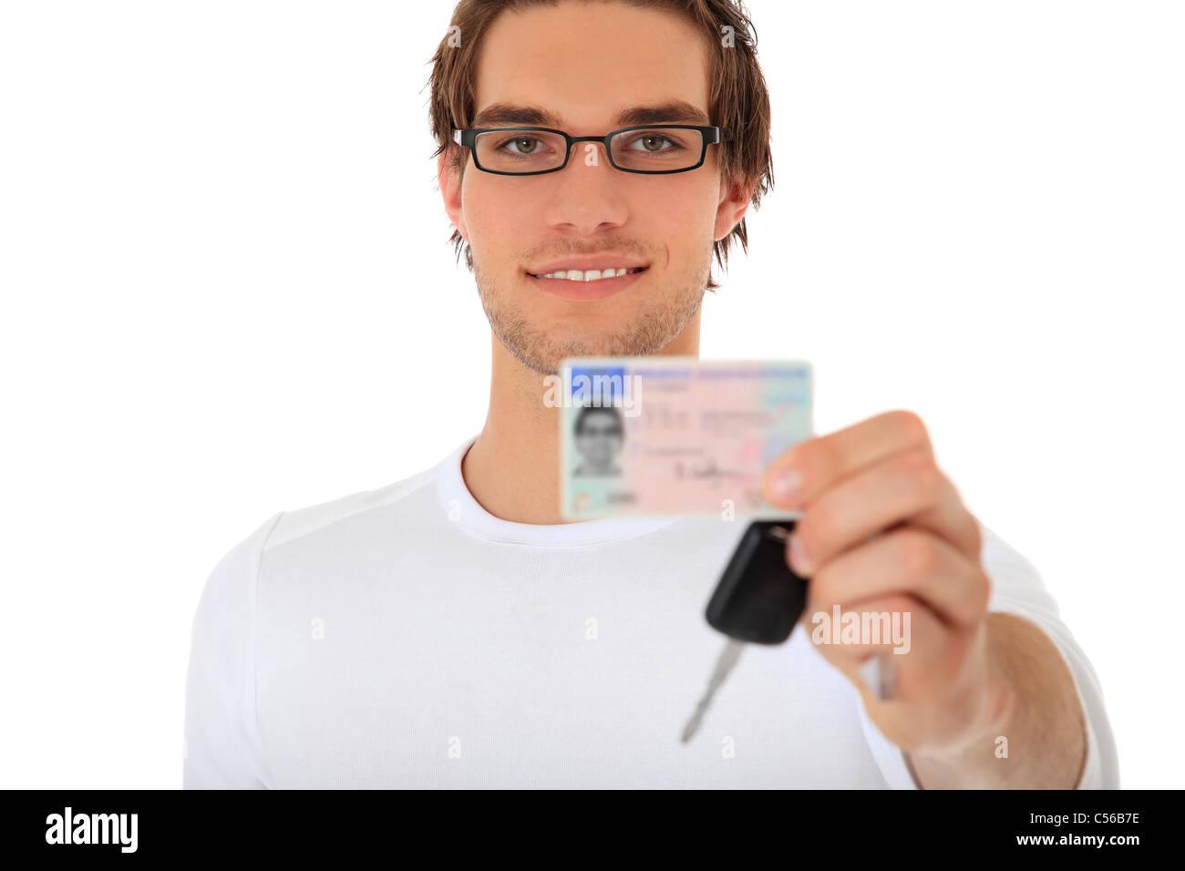 Joven mostrando su licencia de conducir y las llaves del coche. El enfoque selectivo en persona en segundo plano. Imagen De Stock