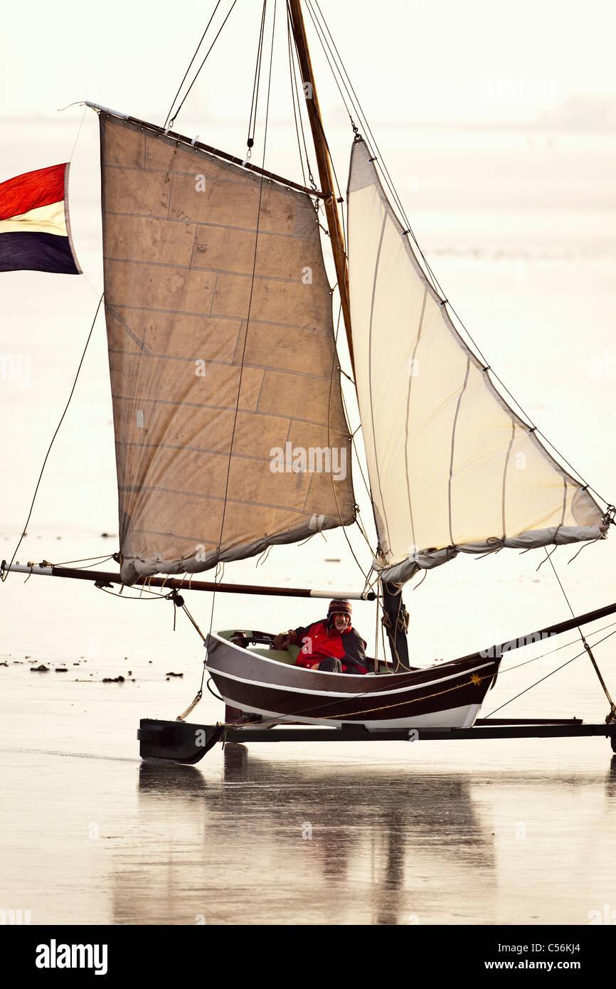 Los Países Bajos Monnickendam, barco de vela en hielo congelado llamado lago IJsselmeer. Imagen De Stock