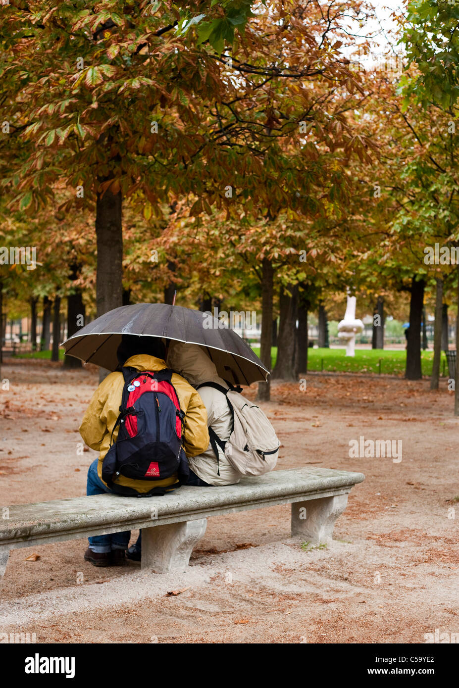 Un par de protegerse de la lluvia en el Jardin des Tuileries. París. Francia Foto de stock