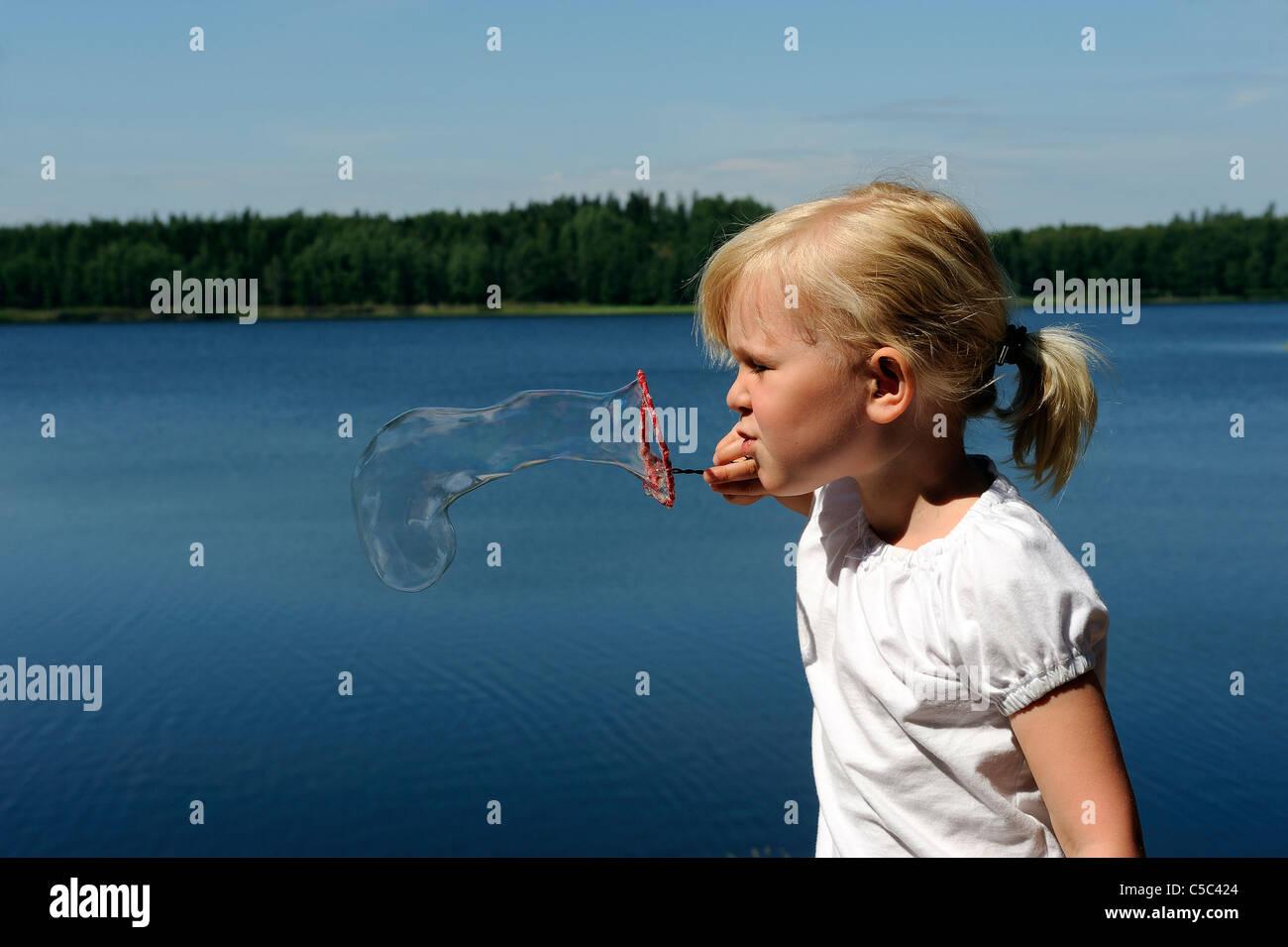 Vista lateral de una chica soplando burbujas de jabón contra el pacífico lago Foto de stock