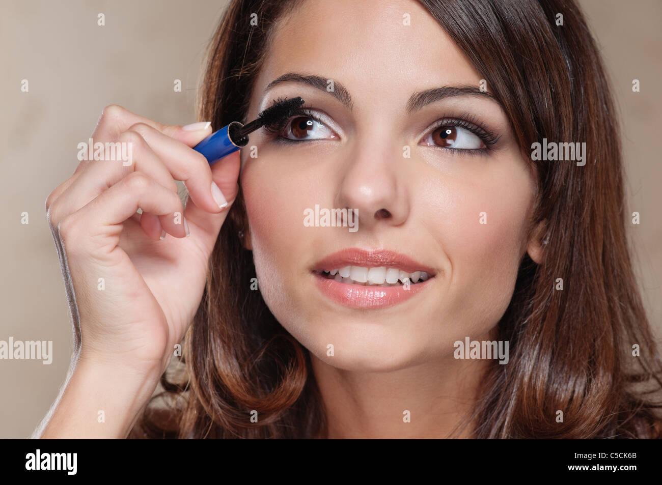 Atractiva mujer joven de aplicar el rímel de sus pestañas Imagen De Stock