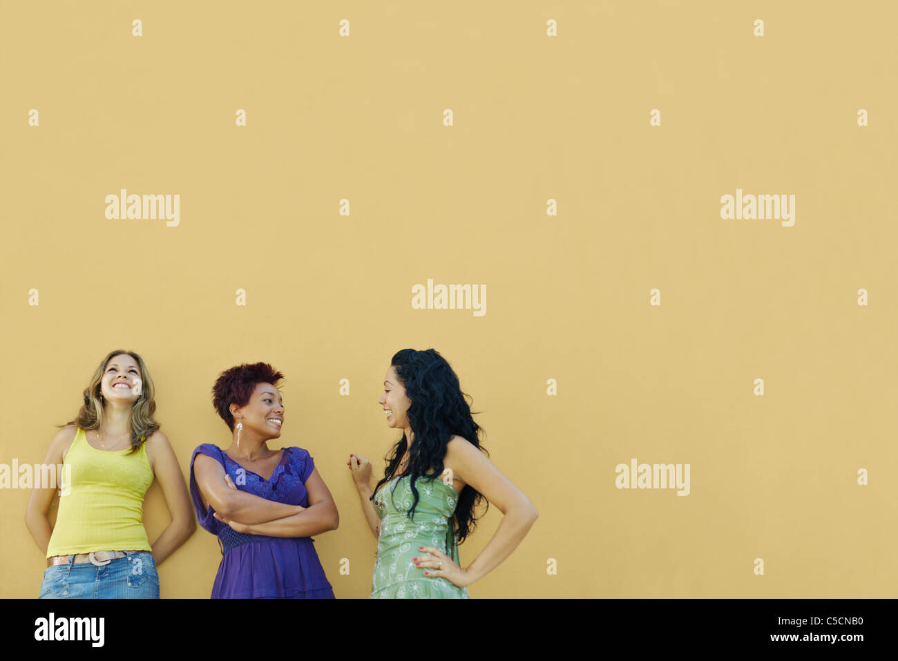 Grupo de tres mujeres amigos hispanos inclinarse sobre pared amarilla y riendo. De forma horizontal, de cintura Foto de stock
