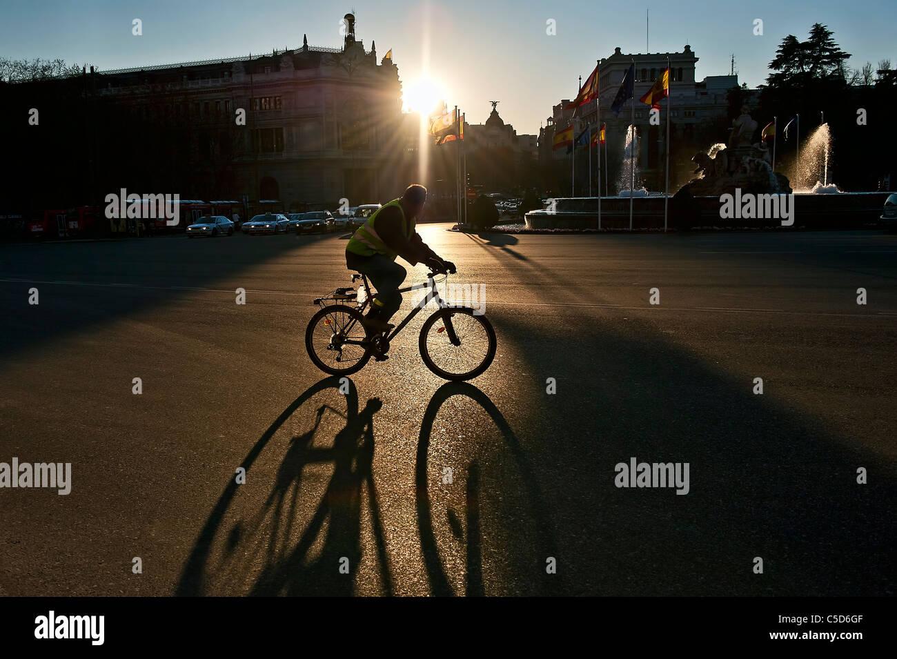 Hombre montado en una bicicleta cuando el sol se levanta, Madrid, España Imagen De Stock