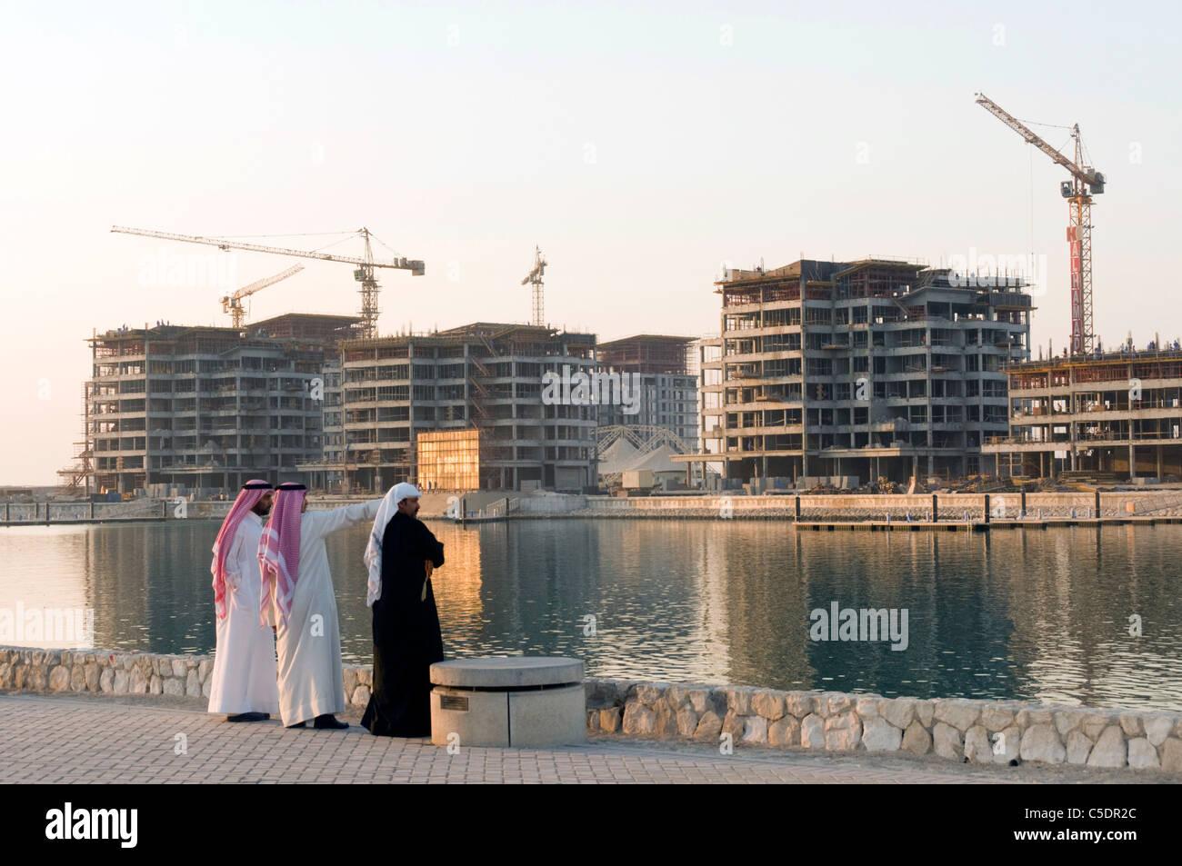 Elk204-1007 Bahrein, Manama, hombres árabes en traje tradicional mirando la construcción de gran altura Imagen De Stock