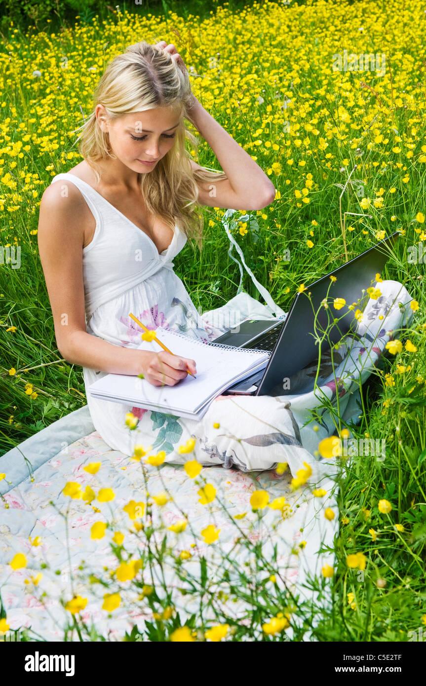 Mujer joven sentada en un hermoso prado florido con un portátil Imagen De Stock