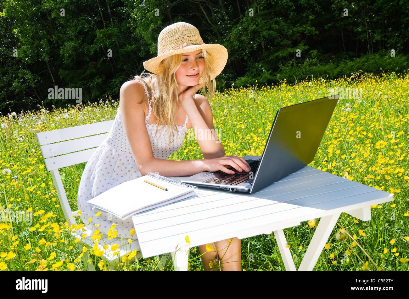 Mujer joven con sombrero sentado en una hermosa pradera floreada con un portátil Imagen De Stock