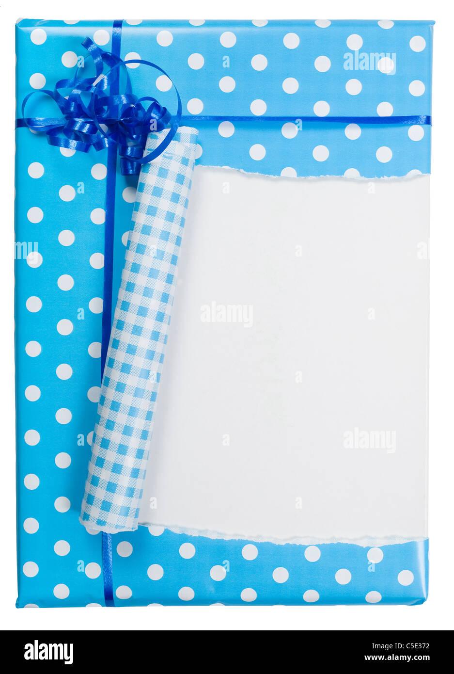 Close-up de un regalo envuelto con papel de embalaje azul roto contra el fondo blanco. Imagen De Stock