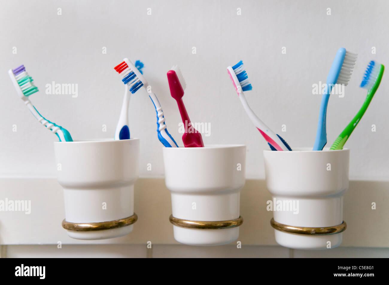 Close-up de cepillos de dientes en tres soportes en fila contra la pared en el cuarto de baño Foto de stock