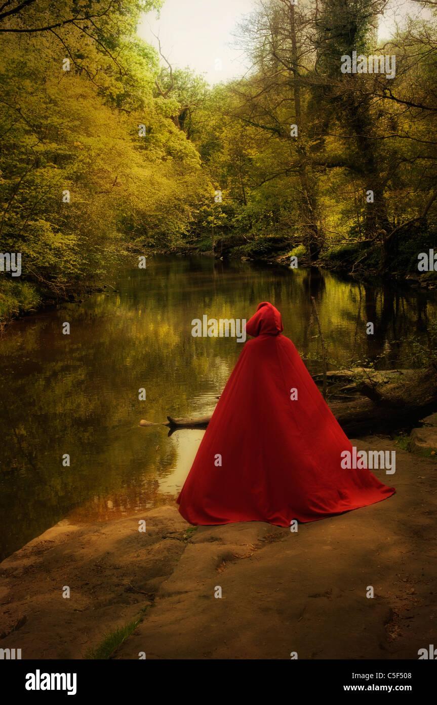 Persona misteriosa en Cabo rojo en el bosque por el lago Foto de stock
