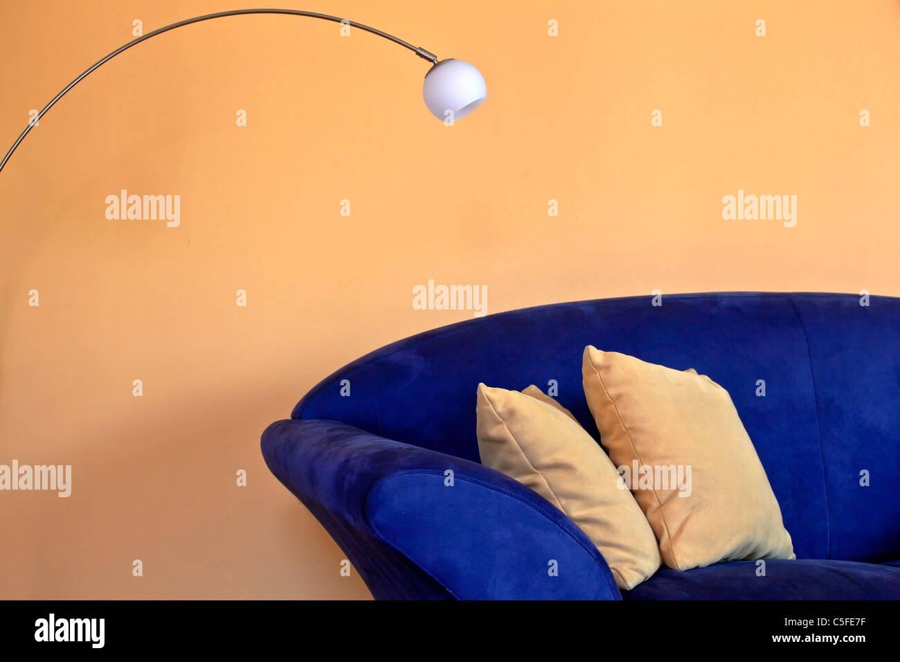 Un sofá azul con lámpara de lectura y almohadas y paredes amarillas Imagen De Stock