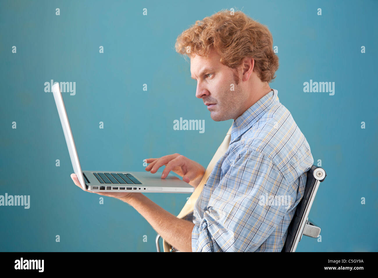 El hombre tiene portátil y tipos Imagen De Stock