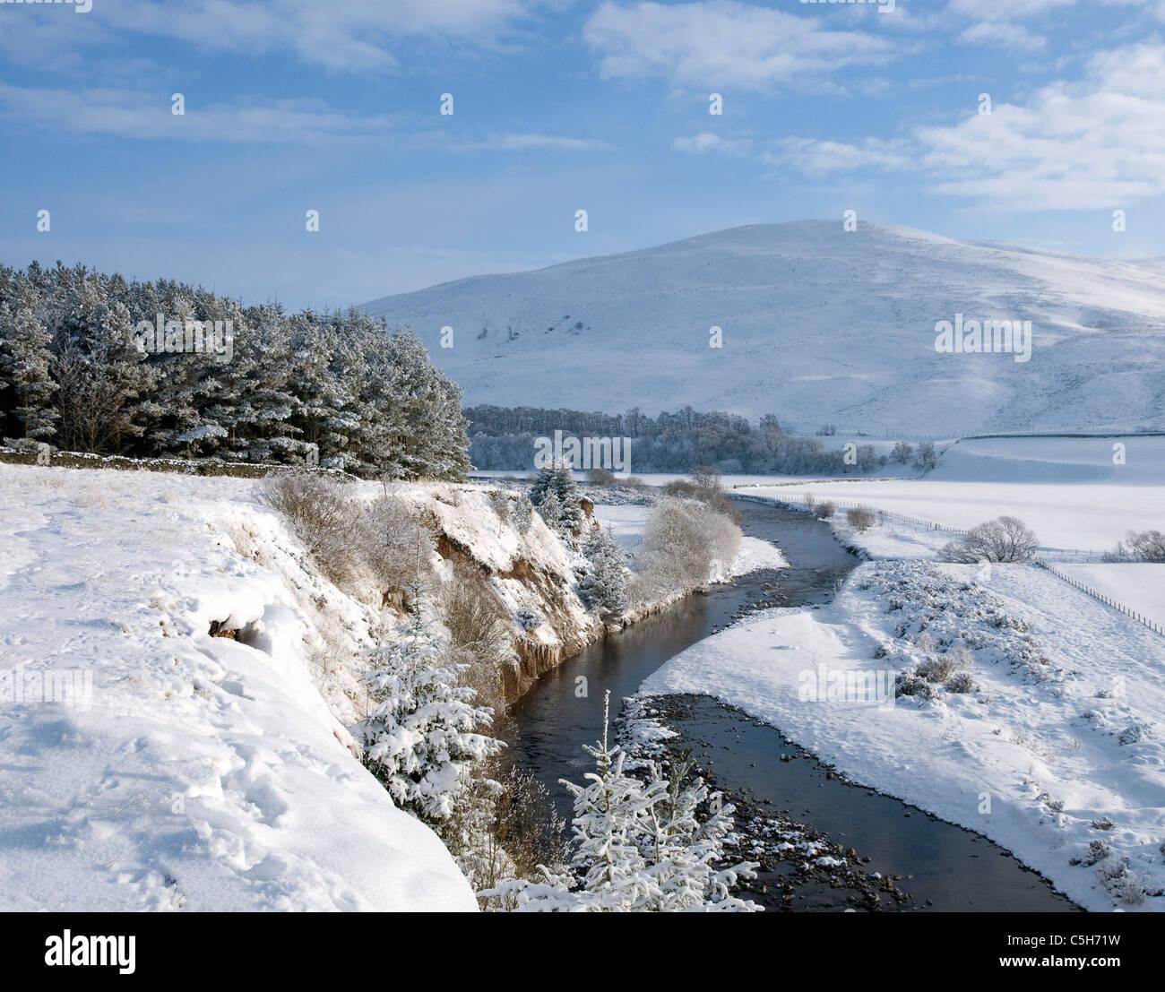 Agua y Yarrow Eldinhope Knowe serpenteando a lo largo de la cañada cerca de Selkirk en nieve Imagen De Stock