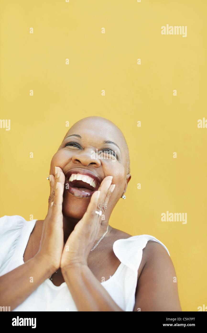 Retrato de africano de 50 años sorprendió a la mujer con cabeza calva, sonriendo sobre fondo amarillo. Imagen De Stock