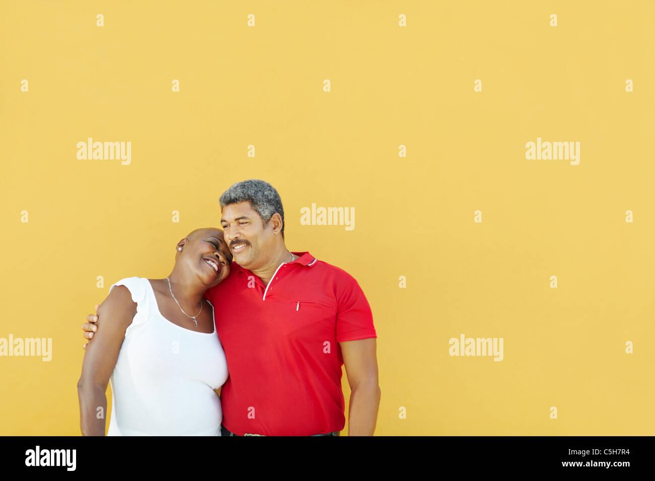 América Latina madura pareja abrazarse y sonriente con pared amarilla en el fondo. Cintura para arriba, el Imagen De Stock