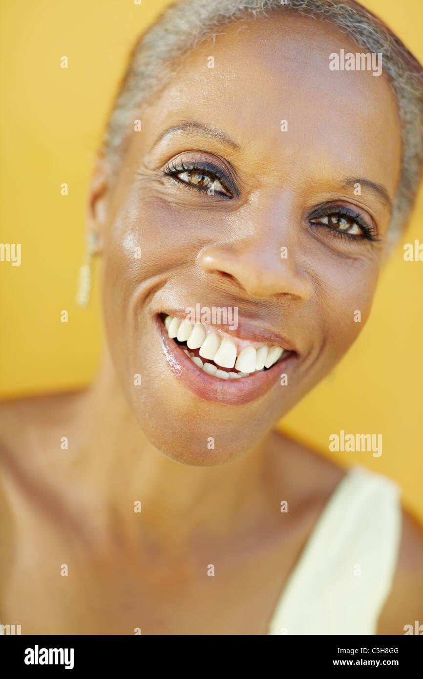 Retrato de africano de 50 años de edad sorprendido mujer sonriente con cabello blanco, sobre fondo amarillo Imagen De Stock