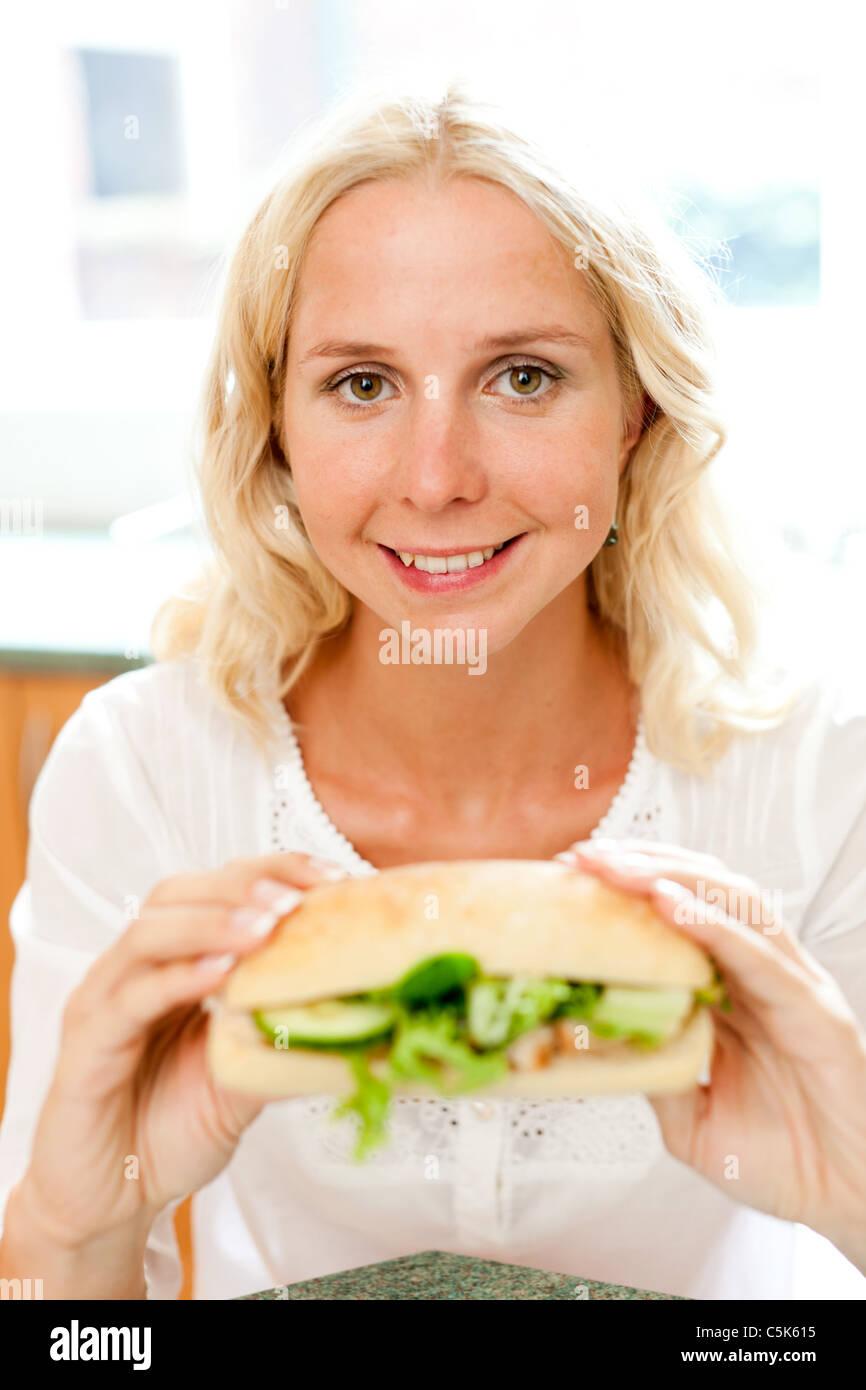 Chica rubia comiendo sándwiches saludables Imagen De Stock