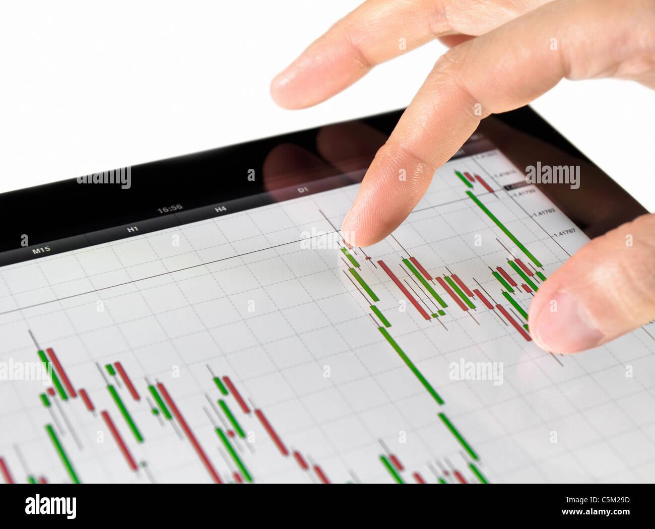 Con la pantalla táctil de Tablet para el análisis gráfico del mercado bursátil. Imagen De Stock