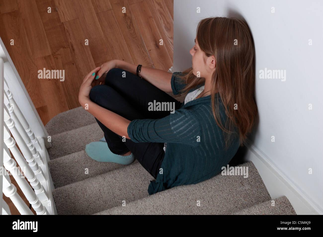 Junge Frauen auf Schritte sitzen allein, allein und suchen etwas traurig Foto de stock