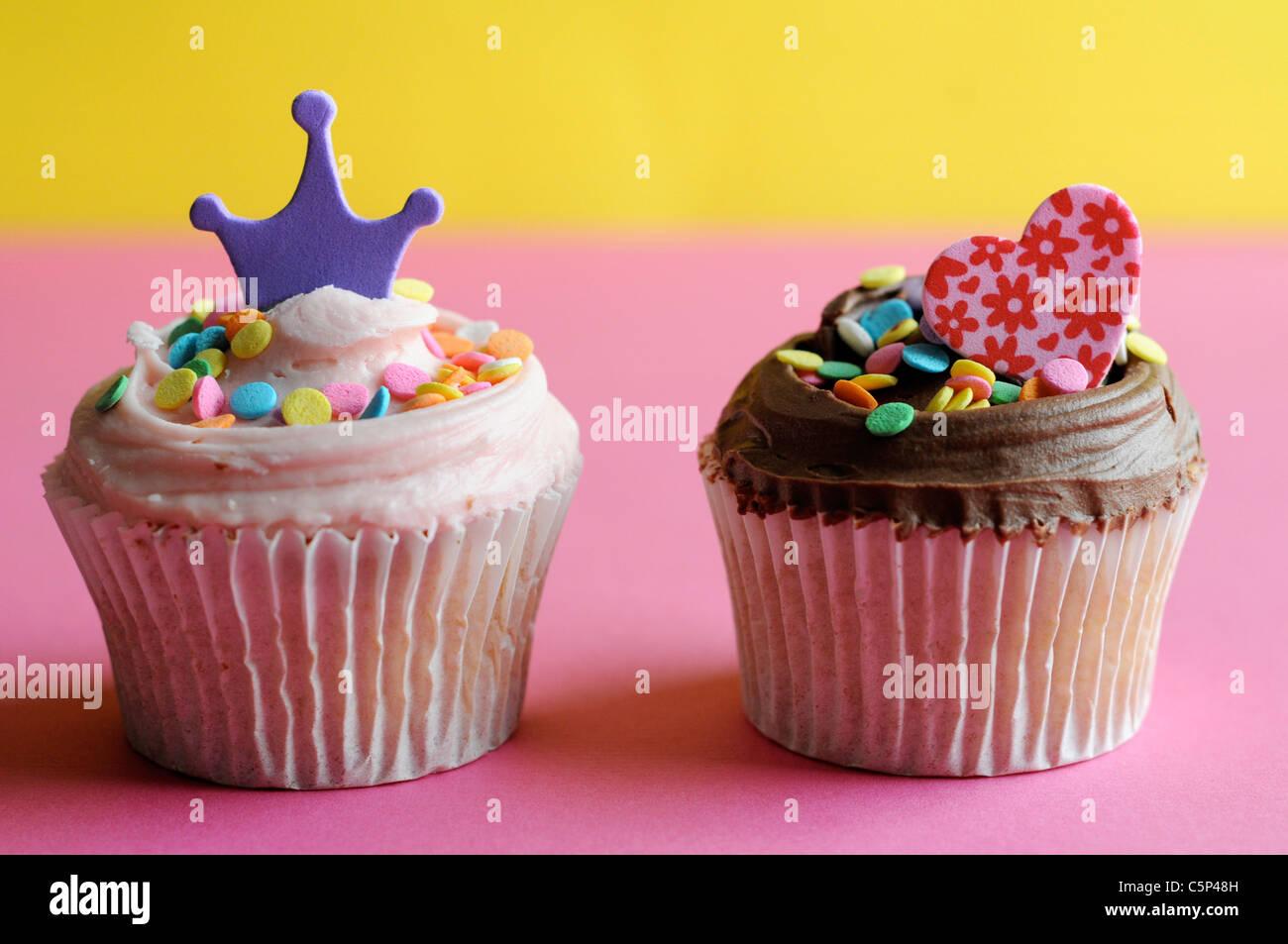 Cupcake de vainilla y chocolate con glaseado y espolvorea azúcar, corazón y corona Foto de stock