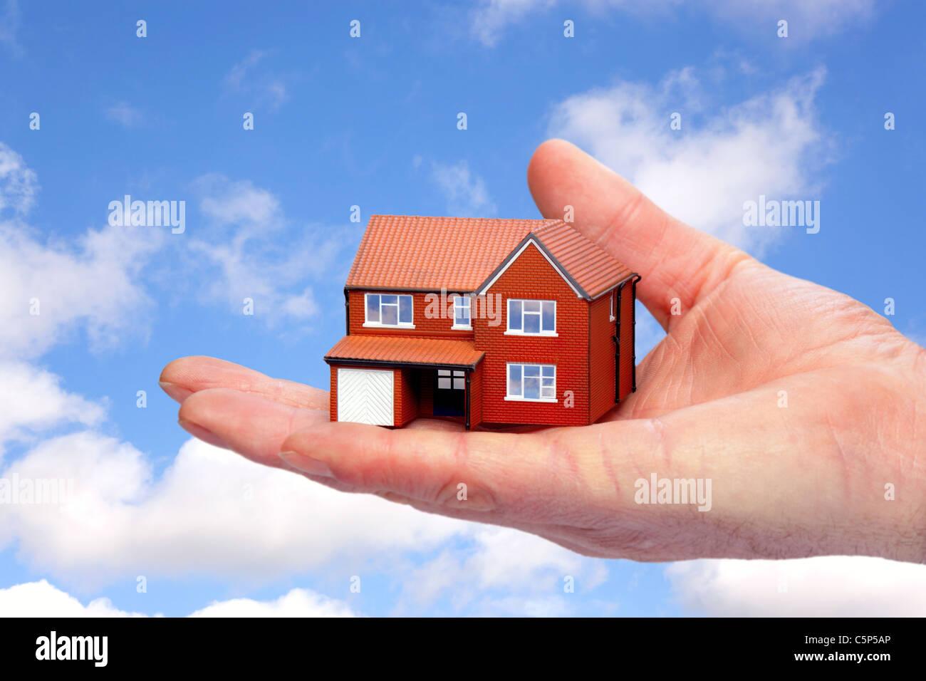 Foto de una mano sujetando una casa modelo contra un fondo de cielo. Foto de stock