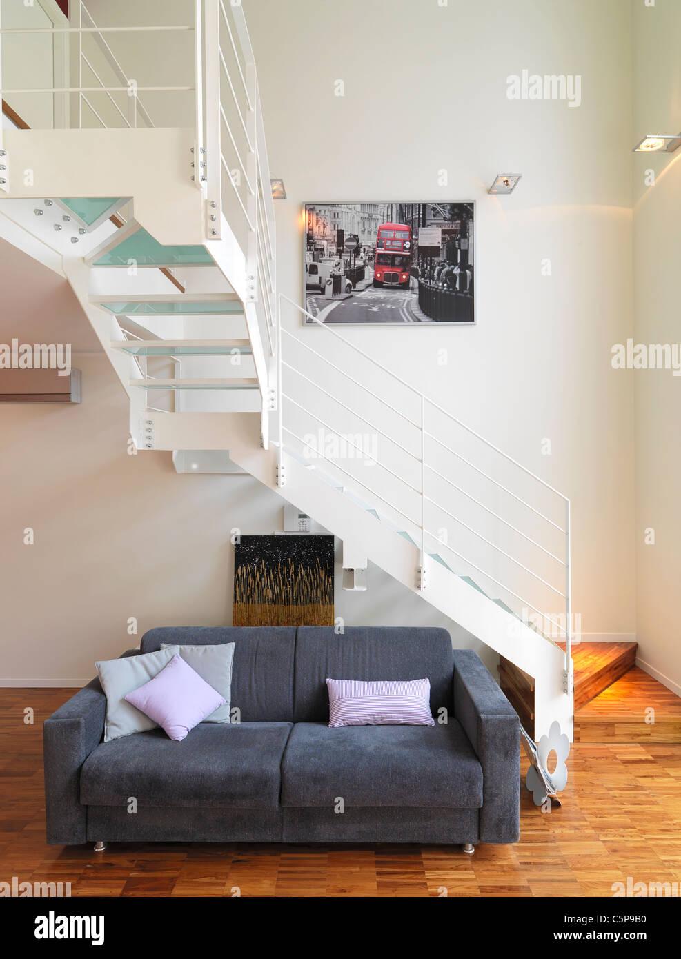 Sofá gris cerca de una escalera con piso de madera en el salón Imagen De Stock