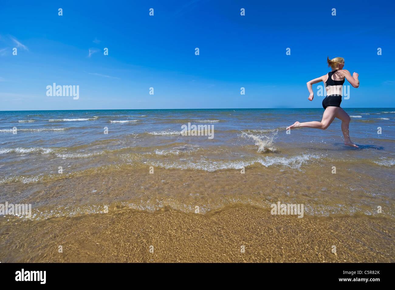 Womans trotar a lo largo de una playa de arena a través de las salpicaduras de las olas del océano. Imagen De Stock