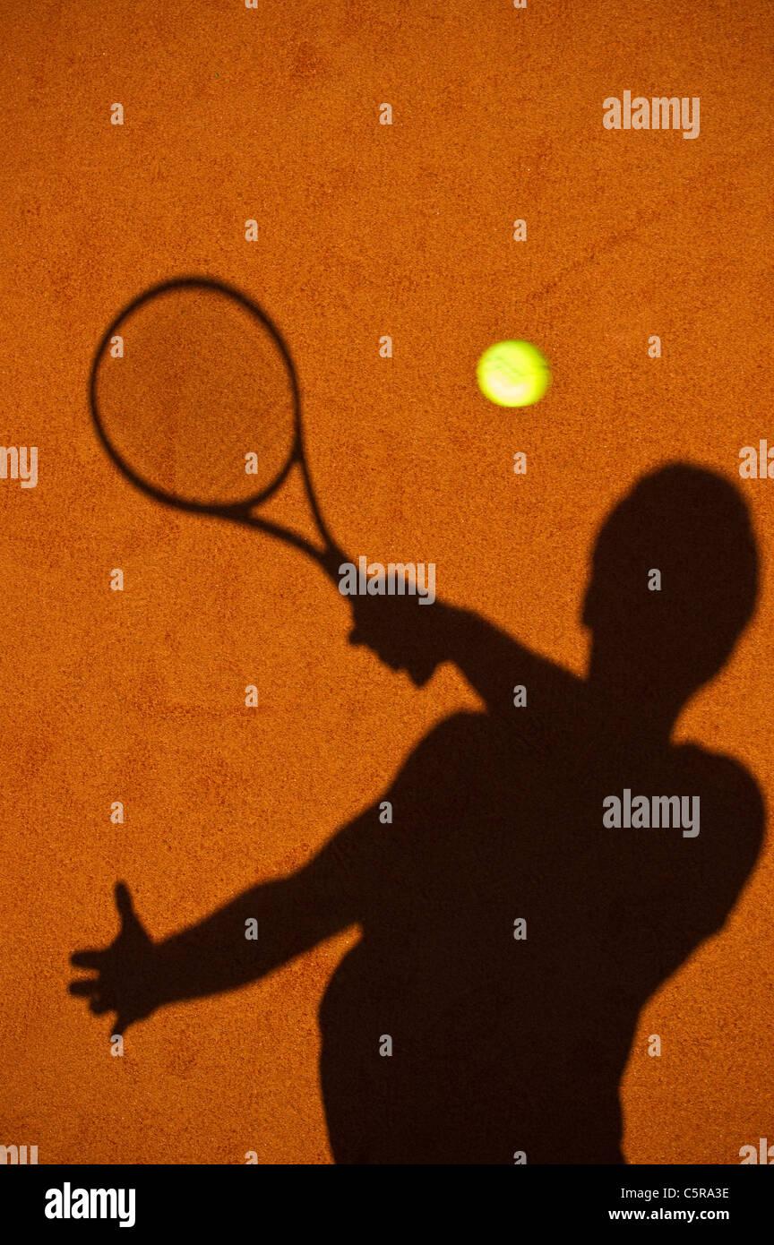Un jugador de tenis silueta jugando el disparo. Imagen De Stock