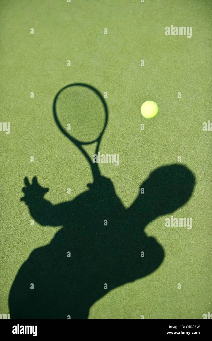 Un jugador de tenis silueta devuelve el balón. Foto de stock