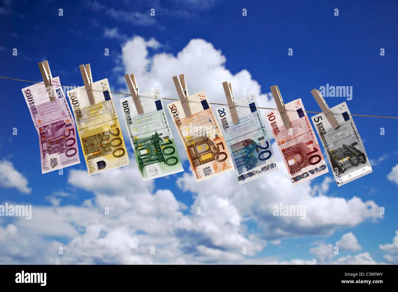 Los diferentes billetes colgando en el tendedero contra el cielo nublado Foto de stock